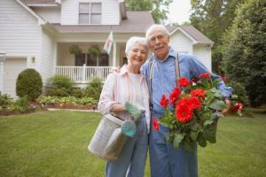 Couple holding watering can and flowers